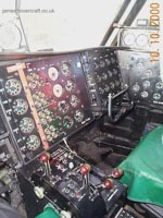 SRN4 systems tour - Here a view of the control cabin as seen from the pilot&#39;s seat&#44; you can see the control column - with four degrees of motion&#58; left & right controlling pylon movement &#40;+/- 30&deg; from normal&#41;&#44; in and out controlling hoverheight and propeller pitch amount interchangeably. <br><br>Also seen are eight red/brown levers. These control&#44; from left to right&#58; Propeller pitch on each propeller&#58; Positive&#44; Zero and Negative; Engine throttle from idle to full power. A selection switch also exists to control whether all four pylons would move synchronously&#44; or whether just the rear two pylons would swivel. <br><br>At the bottom of the two foot wells are the rudder pedals&#44; controlling the angles of the two rear fins to the airflow. <br><br>The pilot and first officer&#39;s control column and rudder pedals are mechanically linked to each other&#44; guaranteeing synchronous operation at all times. <br><br>More detail on each of these controls is on the Cockpit Tour page.  (James Rowson).